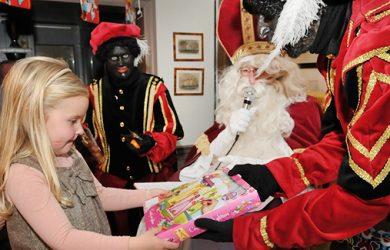 Sinterklaas deelt cadeaus uit.